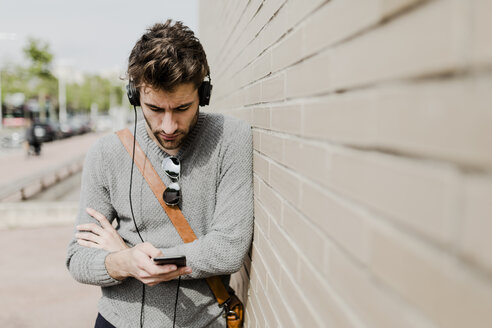 Young man with headphones leaning against wall looking at cell phone - GIOF02972