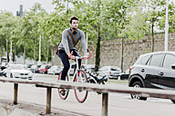 Young man riding racing cycle - GIOF02975