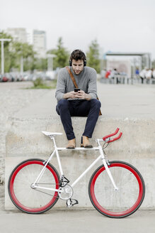 Young man with racing cycle sitting on a wall listening music with headphones - GIOF02978