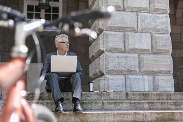 Senior businessman sitting on stairs outdoors working with laptop - GUSF00048