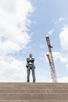 Senior businessman standing on stairs besides construction crane - GUSF00051