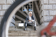 Senior businessman with bicycle sitting on stairs outdoors with laptop and travel mug - GUSF00057