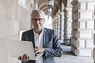 Portrait of senior businessman holding laptop - GUSF00060