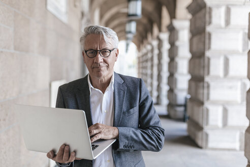 Portrait of senior businessman holding laptop - GUSF00060