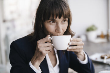 Businesswoman sitting in cafe, drinking coffee - KNSF01892