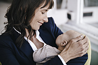 Businesswoman in cafe holding sleeping baby - KNSF01895
