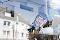 Businesswoman sitting in cafe, daydreaming - KNSF01904