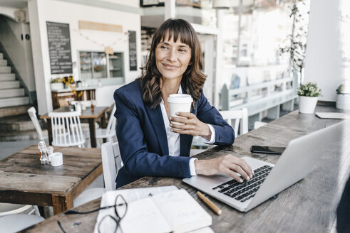 Businesswoman sitting in cafe using laptop and drinking coffee - KNSF01907