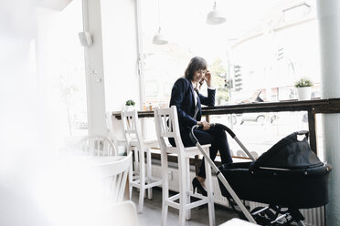 Businesswoman working from cafe with pram on her side - KNSF01910