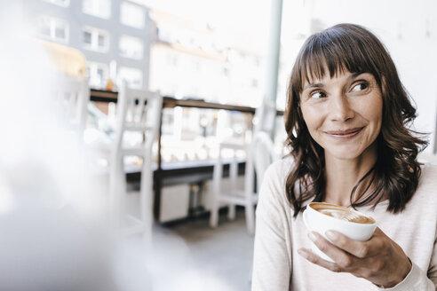Woman in cafe, drinking coffee - KNSF01922