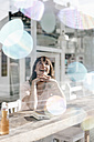 Woman sitting cafe, watching soap bubbles - KNSF01934