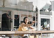 Woman sitting in cafe, writing the word 'coffee' on window pane - KNSF01940