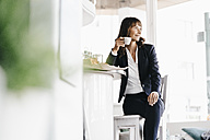 Businesswoman sitting in cafe, drinking coffee - KNSF01946