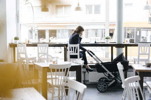 Businesswoman working from cafe with pram on her side - KNSF01964