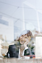 Businesswoman sitting in cafe with laptop, smiling and thinking - KNSF01970