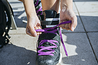 Close-up of woman putting on inline skates - KIJF01635