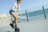 Young woman inline skating on boardwalk at the coast - KIJF01638