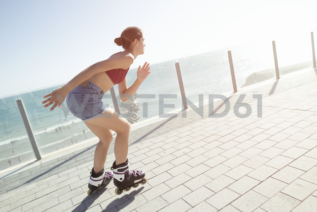Young woman inline skating on boardwalk at the coast - KIJF01641