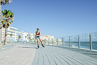 Young woman inline skating on boardwalk at the coast - KIJF01644