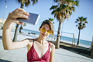 Young woman wearing yellow sunglasses taking a selfie on boardwalk - KIJF01647