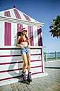 Young woman on inline skates leaning against kiosk - KIJF01653