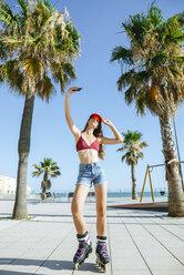 Young woman on inline skates taking a selfie on boardwalk - KIJF01656