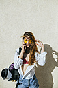 Young woman with inline skates in bag talking on cell phone - KIJF01662