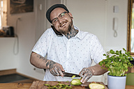 Smiling man on the phone chopping vegetables in the kitchen - GUSF00065