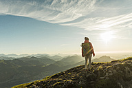 Austria, Salzkammergut, Hiker standing on summit, looking at view - UUF11009