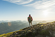 Austria, Salzkammergut, Hiker standing on summit, looking at view - UUF11015