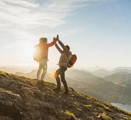 Austria, Salzkammergut, Cheering couple reaching mountain summit - UUF11024