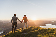 Austria, Salzkammergut, Couple standing on mountain summit, enjoying the view - UUF11048