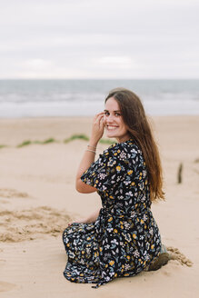 Portrait of happy young woman sitting  on the beach - NMSF00129