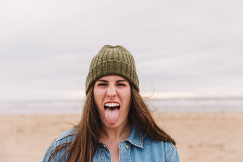 Portrait of woman sticking out tongue on the beach - NMSF00132