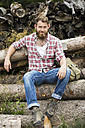 Portrait of bearded man sitting on stack of wood - MAEF12379