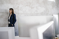 Businesswoman leaning against office wall with hands in pockets - KNSF02004