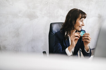 Businesswoman sitting at desk, holding child's pacifier - KNSF02019