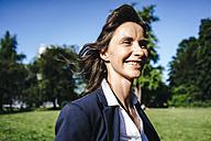 Portrait of a businesswoman walking in the park - KNSF02022