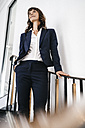 Successful businesswoman standing on staircase - KNSF02034