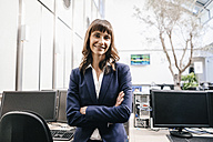 Successful businesswoman standing in office with arms crossed - KNSF02037