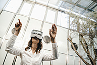 Businesswoman using VR goggles in office - KNSF02043