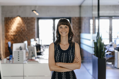Businesswoman standing in office with arms crossed - KNSF02055
