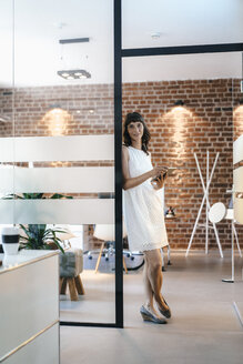 Businesswoman standing in office, holding digital tablet - KNSF02064