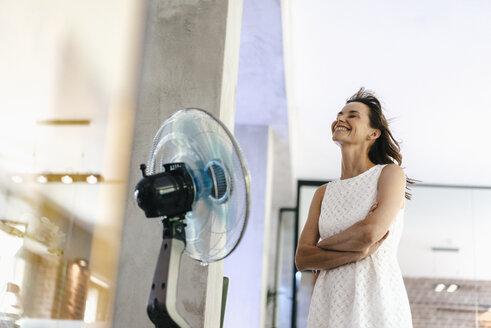 Businesswoman in office enjoying breeze from a fan - KNSF02067