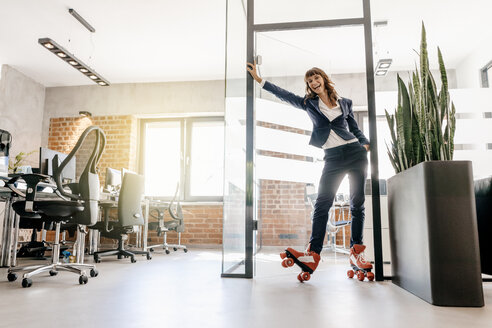 Successful businesswoman wearing roller skates in office - KNSF02091