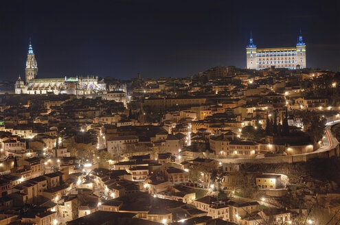 Spain, Toledo, view to lighted cityscape with cathedral and Alcazar in the background at night - DHCF00089