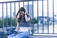 Young woman sitting on a bridge looking at cell phone - UUF11060