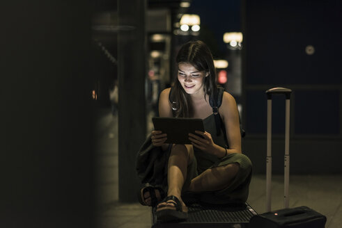 Smiling young woman with tablet waiting at station by night - UUF11066