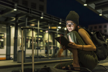 Portrait of young woman with headphones and tablet waiting at station by night - UUF11069