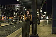 Young woman waiting at the station by night using cell phone - UUF11072